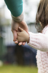Cropped image of mother holding daughter's hand at park