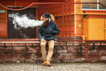 Vape bearded man in real life. Portrait of young guy with large beard in glasses and a cap vaping an electronic cigarette and letting steam opposite the fence in the autumn.