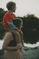 Side view of mother carrying son on shoulders while standing at lakeshore during sunset