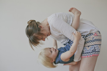 Side view of mother playing with daughter against gray background