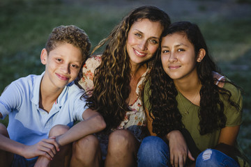 Portrait of happy mother with children sitting at park