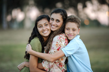Portrait of loving mother and children embracing at park