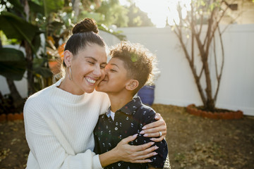 Loving son kissing cheerful mother at backyard