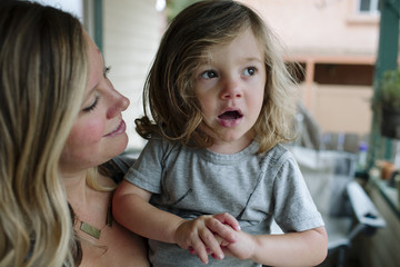 Close-up of mother looking at cute thoughtful daughter on porch