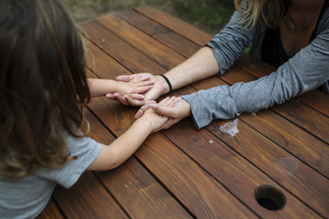 High angle view of mother and daughter holding hands on wooden table at backyard