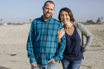 Portrait of cheerful couple standing at beach
