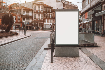Vertical empty billboard placeholder template on pavement stone street with metro entrance behind and city road on the left; blank advertising banner mockup in urban settings on a winter day