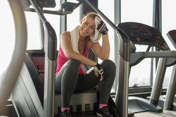 Exhausted woman at the gym wiping off sweat