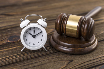 The concept of a clock and a hammer by the judge. Idea: the time of the trial, the Verdict.