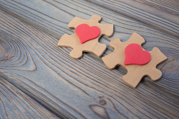 two pieces of a puzzle with a red heart, unite into a single whole. Holiday, St. Valentine's Day, lovers' day, close-up