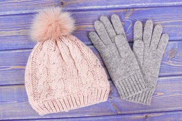 Woolen womanly gloves and cap for woman on old purple boards
