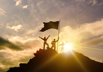 High success, family three silhouette, father of mother and child holding flag of victory on top of mountain, hands up. A man on top of a mountain. Conceptual design.