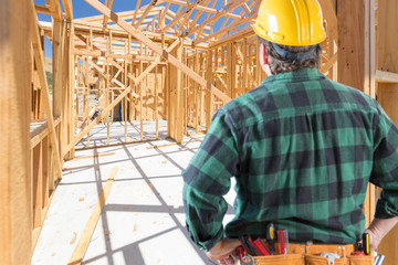 Contractor Standing Inside Construction Framing of New House.