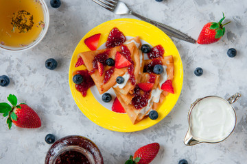 Two thin pancakes, folded in triangles, are poured with sour cream, jam and decorated with fresh berries. The concept of Russian holiday Maslenitsa