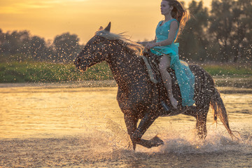 Girl riding horse on water surface