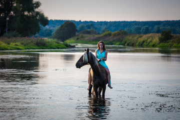 A girl in blue dress sitting on a horse in water