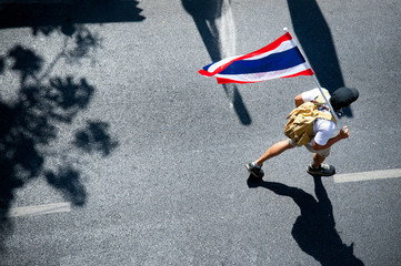 A man walking on street with Thai Flag on shoulder, political activist