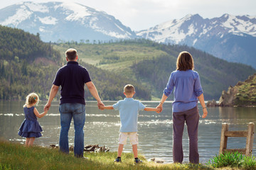 back of family holding hands looking at lake and mountains