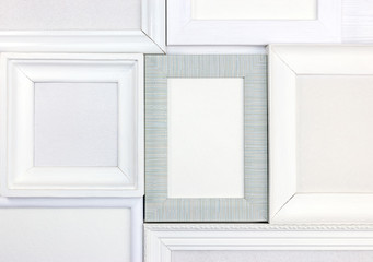 different white and gray empty wooden photo frames as background