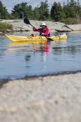 Active senior paddling a sea kayak
