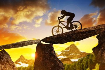 Silhouette of a girl riding a mountain bike at sunset.