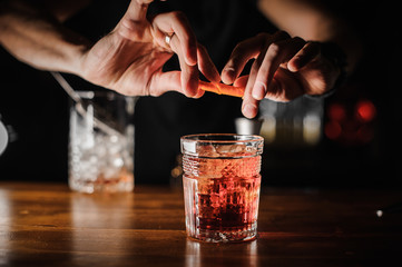 barman preparing alcoholic cocktail negroni of pink color with ice