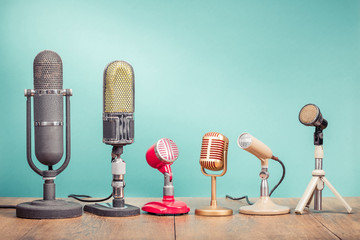 Retro old microphones for press conference or interview recording on table front gradient aquamarine background. Vintage old style filtered photo