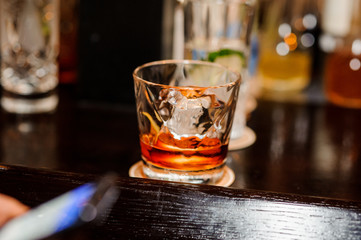 half-empty glass with whiskey and ice stands on a brown wooden bar counter