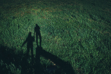 The shadow is held by the hand. Field of green fresh grass. Wide plan.