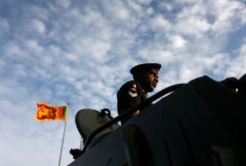 An Army soldier looks on from a tank, as Sri Lanka's national flag is seen in the background, at the parade during a rehearsal for Sri Lanka's 70th Independence day celebrations in Colombo