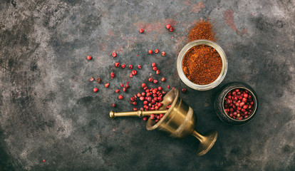 Pink peppercorns and powder and a bronze mortar on metal rusty background, top view, copy space