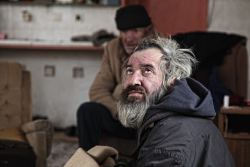 Poor homeless men sitting in abandoned house
