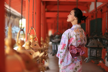 a young Japanese woman in summer kimomo (yukata) with traditional lanterns in a traditional Japanese building Wall mural