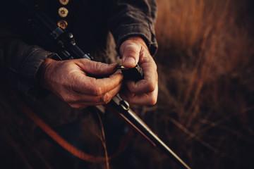 Close up of hunter loading his shotgun with bullets