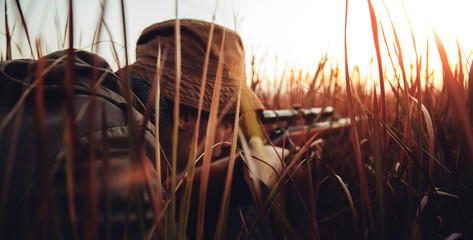 Hunter with rifle laying in long grass and concentrating on shooting prey