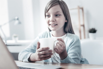 Cozy leisure time. Charming little girl focusing her attention on a screen of a laptop while sitting at a table and warming up with a cup of warm tea.