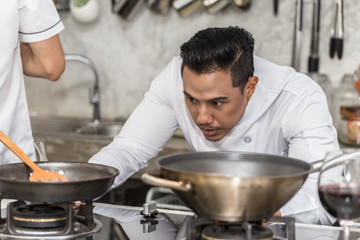 Asian handsome Chef preparing for cooking food in restaurant