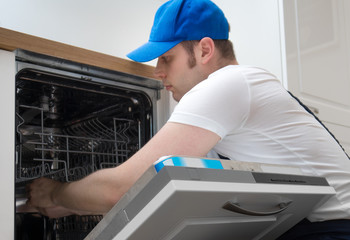 Professional handyman in overalls repairing domestic dishwasher in the kitchen.