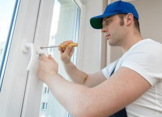 Professional handyman fixing window handle at home.