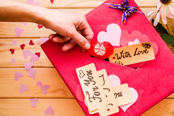valentine's day concept. woman's hand putting an origami paper heart to a valentine box