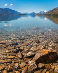 Beautiful alpine view with snow-capped mountains from the shore of Lake Wakatipu, New Zealand.