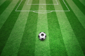 Soccer ball on sunny football field pattern background.