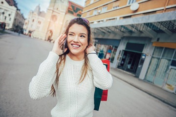 Beautiful woman with shopping bags in the city using smart phone