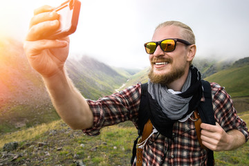 Man Traveler With Beard Makes Selfie In The Background Of A Mountain Landscape. Journey Hiking Concept