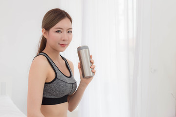 Sporty Asian young woman with drinking water after work out