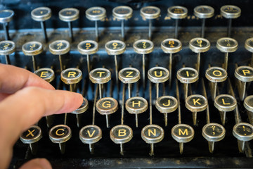 old typewriter keyboard close-up with fingers typing - vintage antique style typewriter