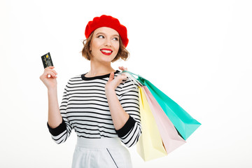 Happy young woman holding credit card and shopping bags