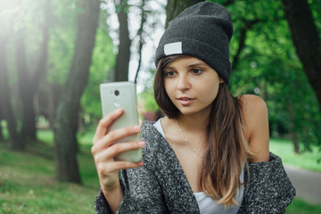 Młoda kobieta robi sobie selfie w parku.
