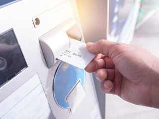 Hand inserting card into automatic teller machine to withdraw money
