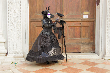 Venetian Mask of Woman with Bird in black elegant costume on on San Zaccaria Square in Venice.